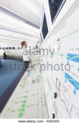 Engineer pointing to computer monitor in control room of nuclear power station - Stock Photo