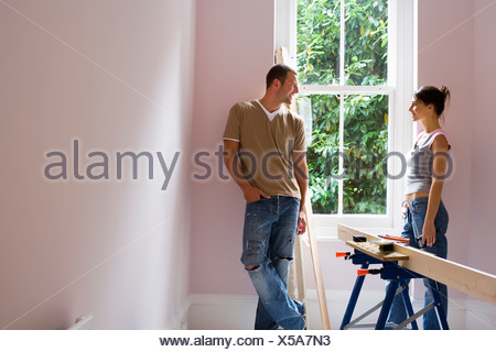 Couple doing DIY at home standing beside window woman holding glue gun near timber on workbench - Stock Photo