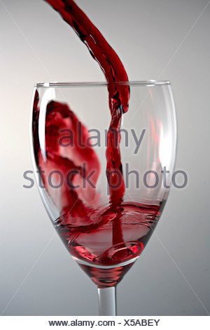 Close-up of red wine being poured in glass against gray background Stock Photo