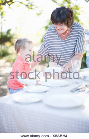 Boy and grandmother setting dinner table outdoors - Stock Photo