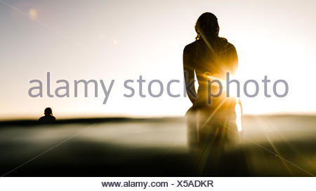 Silhouette of two surfers at sunrise - Stock Photo