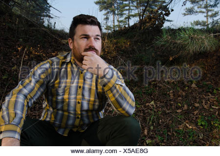 Young man contemplating in forest - Stock Photo