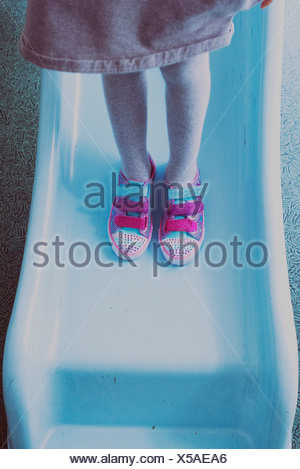 Girl standing on slide, wearing colorful sneakers, low section - Stock Photo