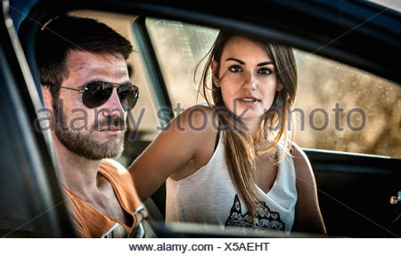 Close up of young couple through car window - Stock Photo