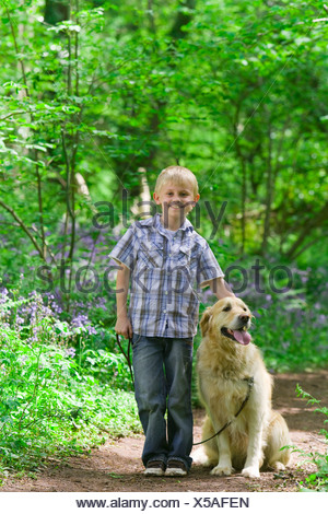 Boy and dog posing in forest among bluebell flowers - Stock Photo