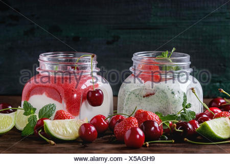 Two Square glass jars with homemade yogurt with mint, strawberry puree, cherry and chia seeds served with fresh berries  and sli - Stock Photo