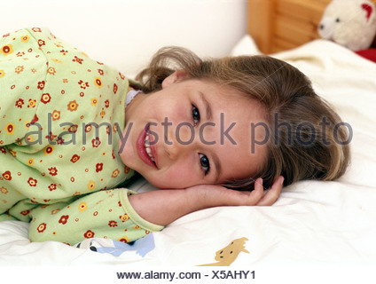 Young girl laying on bed smiling, portrait. - Stock Photo