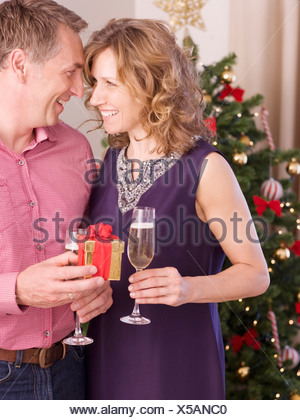 Couple holding champagne and gift near Christmas tree - Stock Photo
