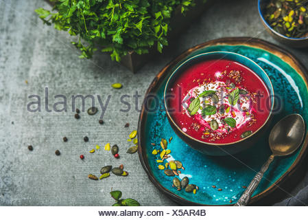 Spring detox beetroot soup with mint, chia, flax and pumpkin seeds on bright blue ceramic plate over grey concrete background, copy space. Dieting, cl - Stock Photo