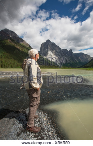 Man Stands On The Shores Of Glacier Lake; Northwest Territories, Canada - Stock Photo