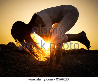Woman practicing yoga on beach at sunset - Stock Photo