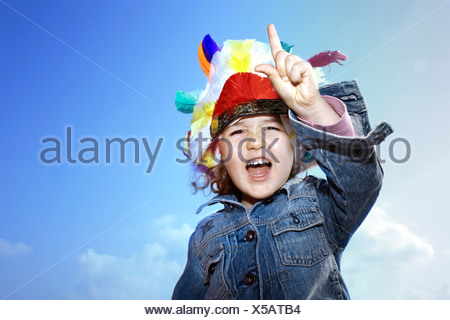 Toddler girl wearing Indian headdress - Stock Photo