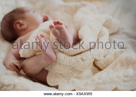 Sleeping baby lying on bed - Stock Photo