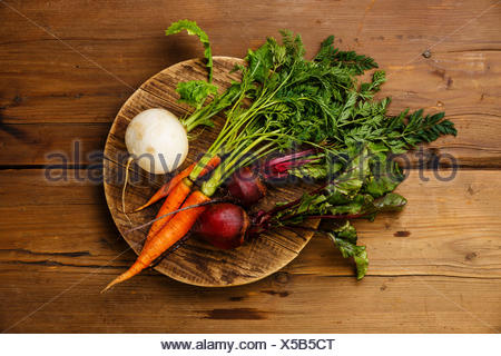 Fresh vegetables carrots, turnip and beets on round cutting board on wooden background - Stock Photo
