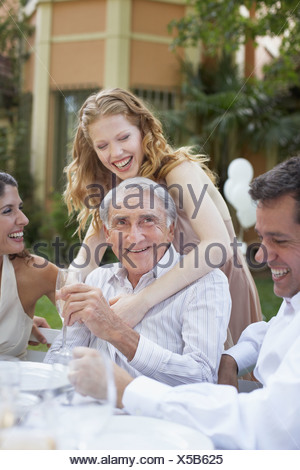 Woman and senior man at outdoor party being affectionate and smiling - Stock Photo