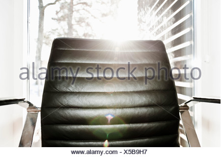 Leather armchair in backlight - Stock Photo