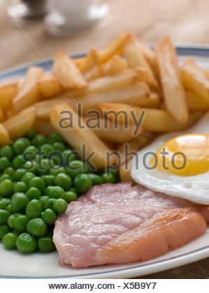 Gammon Steak Fried Egg Peas and Chips - Stock Photo