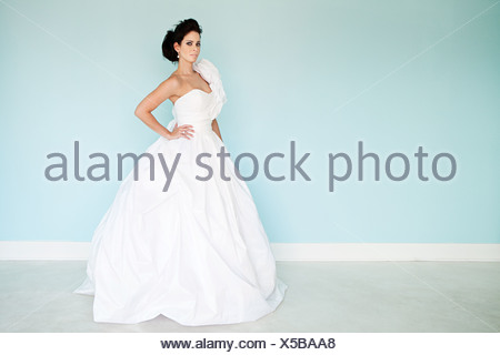 Young woman wearing white wedding dress, studio shot - Stock Photo
