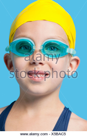 Close-up portrait of a happy young girl wearing swim cap and goggles over blue background - Stock Photo