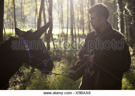 Young man pulling reluctant donkey in forest - Stock Photo