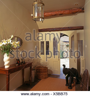 Vase of white lilies on console table in country hall with wooden