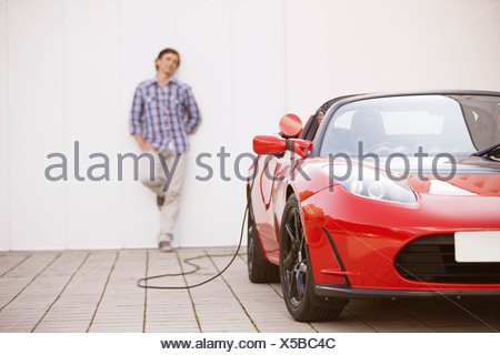Young man filling up his electric car
