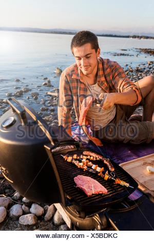 Young man sitting next to water cooking meat and kebabs on barbecue, Schondorf, Ammersee, Bavaria, Germany - Stock Photo
