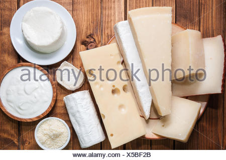 Various cheeses on a wooden board - Stock Photo