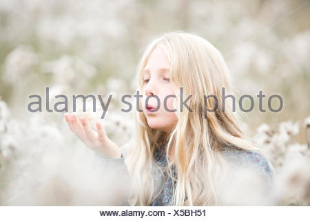 Portrait of girl standing in a field blowing seeds out off her hand - Stock Photo