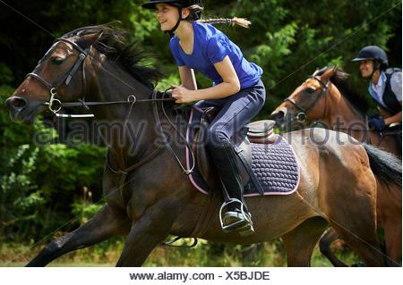 Side view of girl riding horse smiling - Stock Photo