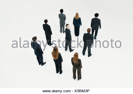 Businessman standing in midst of other anonymously dressed professionals - Stock Photo