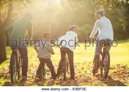 Rear view of a young family doing a bike ride - Stock Photo
