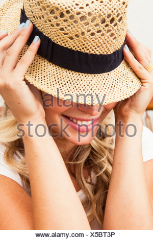 Young woman putting on straw hat - Stock Photo