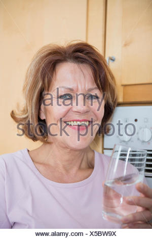 Portrait of senior woman in kitchen with water glass, smiling - Stock Photo