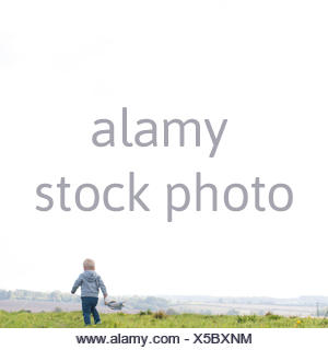 Rear view of boy running in field - Stock Photo