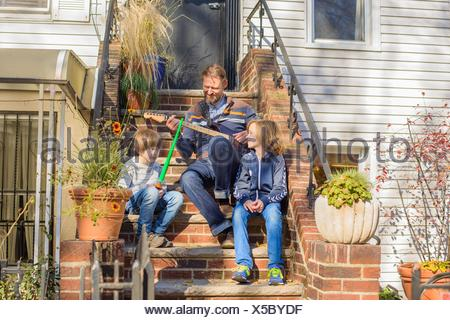 Father and sons sitting together on front steps, father playing guitar - Stock Photo