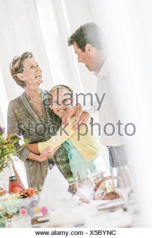 Looking through window at girl hugging grandmother in dining room - Stock Photo
