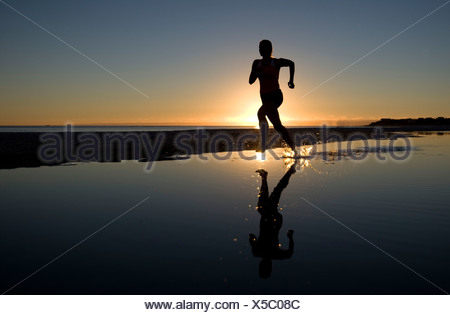Young Woman Running on Beach at Sunset - Stock Photo