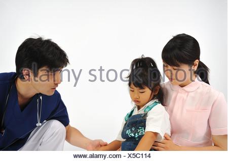 Male doctor and female nurse examining girl - Stock Photo