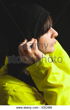 Portrait of young woman wearing yellow raincoat and toque hat - Stock Photo