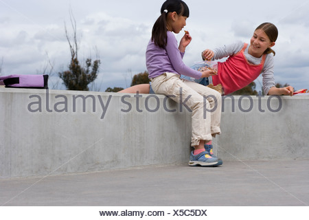 Two girls 9 11 sitting on wall eating packed lunch smiling side view - Stock Photo