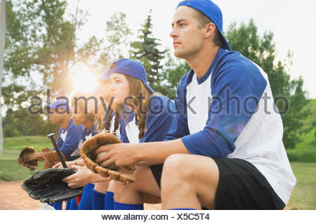 Baseball team sitting together on field - Stock Photo