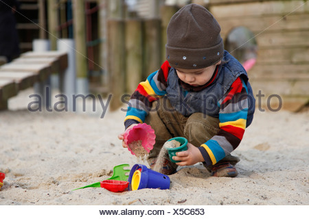 little boy playing in a sandpit with sand moulds - Stock Photo