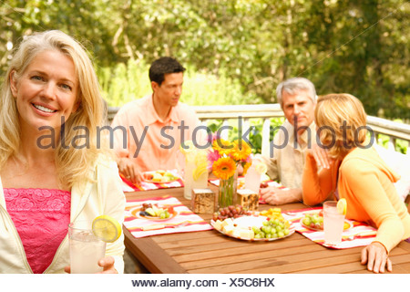 Portrait of a mature woman holding a glass of lemonade with three mature people sitting behind her - Stock Photo