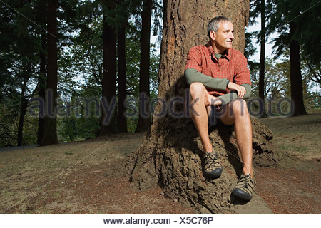 Man sitting by a tree - Stock Photo