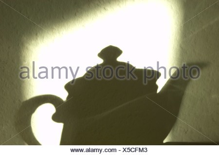 The morning sun is drawing the shaddow of a coffepot on the wall - Stock Photo