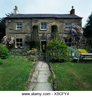 Lawns on either side of stone paved path leading to stone-built country house - Stock Photo