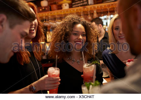 Group Of Friends Meeting For Evening Drinks In Cocktail Bar - Stock Photo