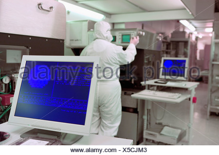 Engineer in clean suit working at machinery in silicon wafer manufacturing laboratory - Stock Photo