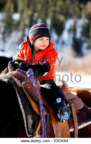 a little boy rides a horse while bundled up in a warm jacket and stocking cap / hat on a cold winter day with snow on the ground - Stock Photo